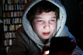 Boy wearing hoodie in dark room using mobile device