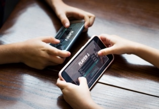Photo of the hands of two youth with phones playing a game