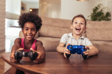 A young boy and a young girl laugh as they play video games