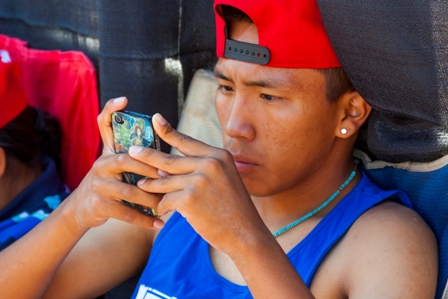 An indigenous male teen looks closely at the screen of his smartphone