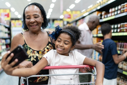 An african american older woman takes a selfie with her granddaughter in a grocery store