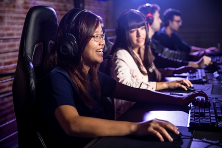 Teen girls sit at computers gaming