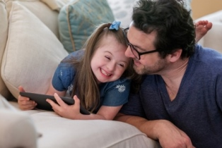 Father and daughter with down syndrome using a tablet