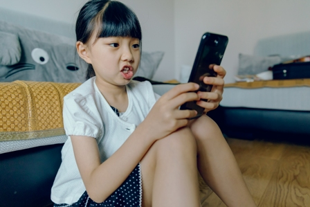 An Asian girl texting on her smart device