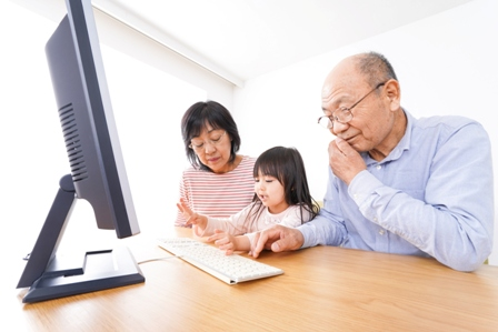 An Asian grandfather sits before a computer screen with his two grandchildren