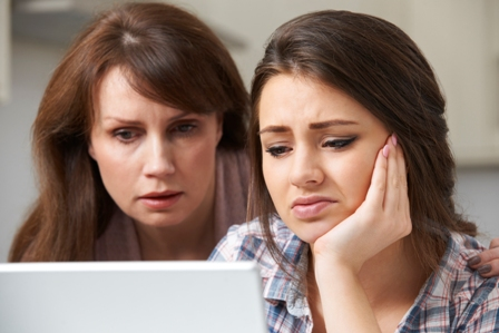 A worried teen girl and her mother look at a computer screen