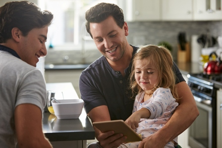 A same sex male couple, with their young daughter, sit at the kitchen island looking at a tablet screen