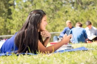 Indigeneous girl in outdoor summer setting using a smartphone
