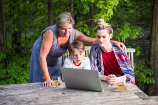 Female with two youth outdoors at picnic table looking at laptop